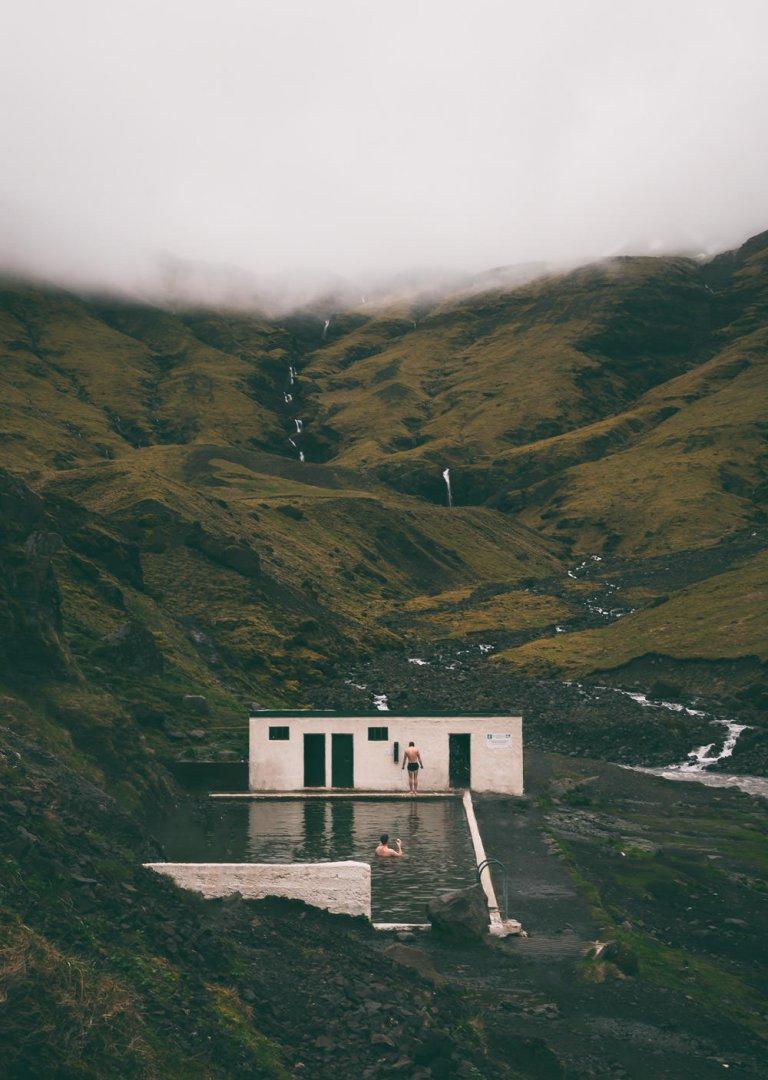 Dwie osoby kąpiące się w basenie termalnym Seljavallalaug na Islandii