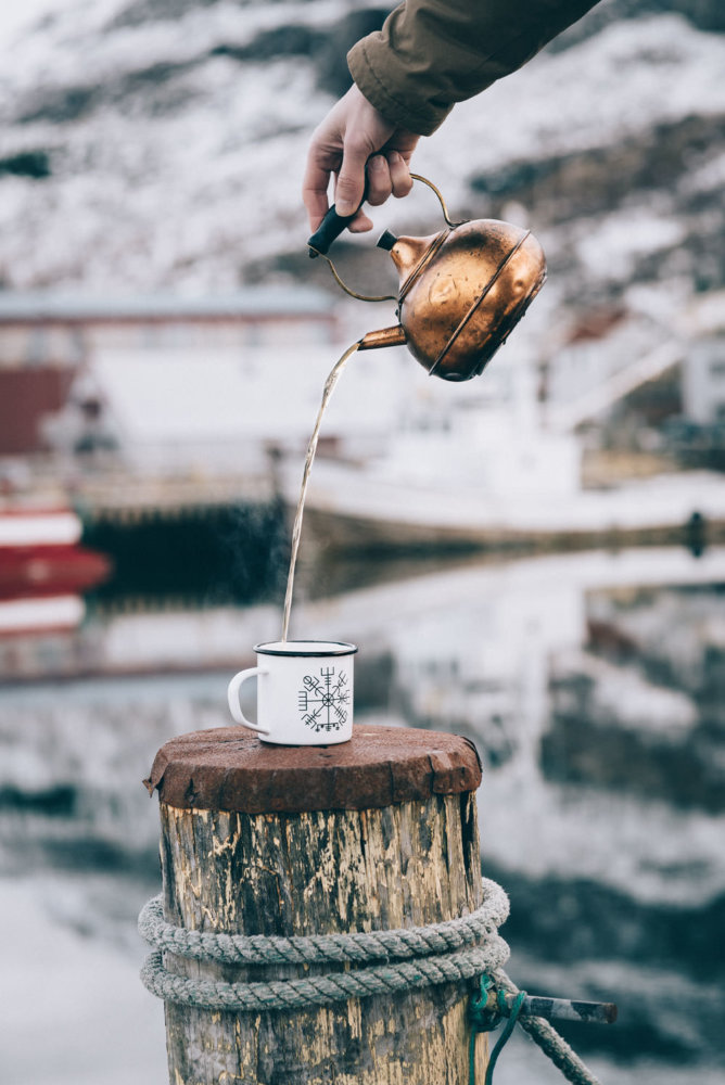 Pouring hot tea by the fishing harbour in Seydisfjordur, Iceland