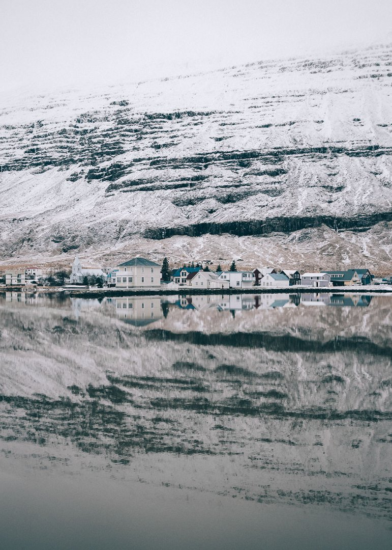 Colourful houses in Seyðisfjörður in the winter, reflecting in the water.