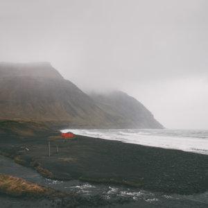 Plakat skandynawski na ścianę do salonu przedstawiający czerwoną chatkę na czarnej plaży. Dostępne wymiary: plakat 50x70 i plakat 30x40. Skandynawski sklep z plakatami.