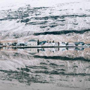 Plakat skandynawski na ścianę do salonu przedstawiający zimę w małym islandzkim miasteczku Seydisfjordur. Zobacz nasze plakaty skandynawskie.